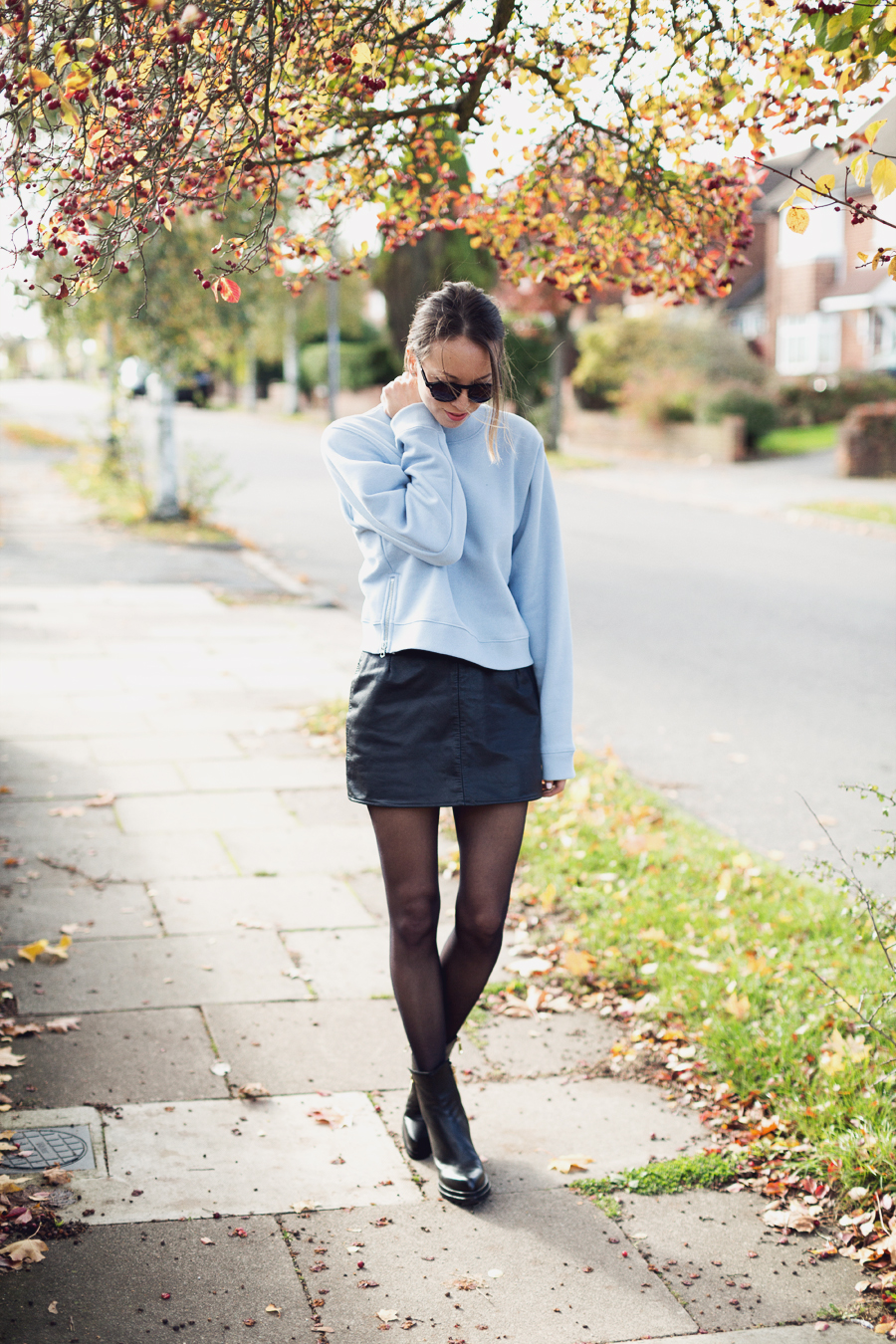 Acne sweatshirt, leather skirt, boots, sunnies