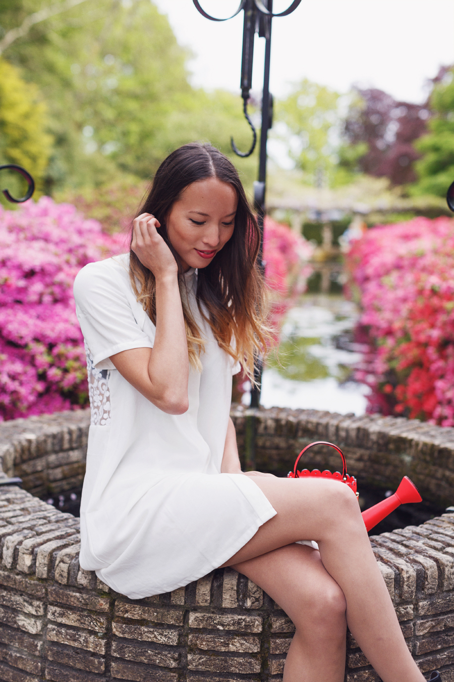 Girl in white shirt dress by wishing well