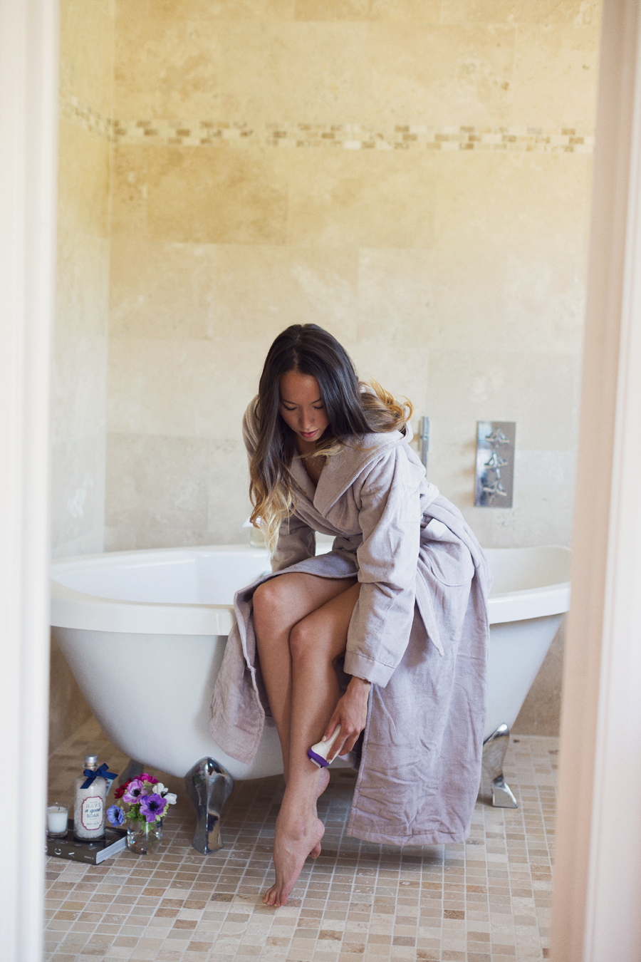 girl in bathrobe shaving legs in a bathroom on a bath tub