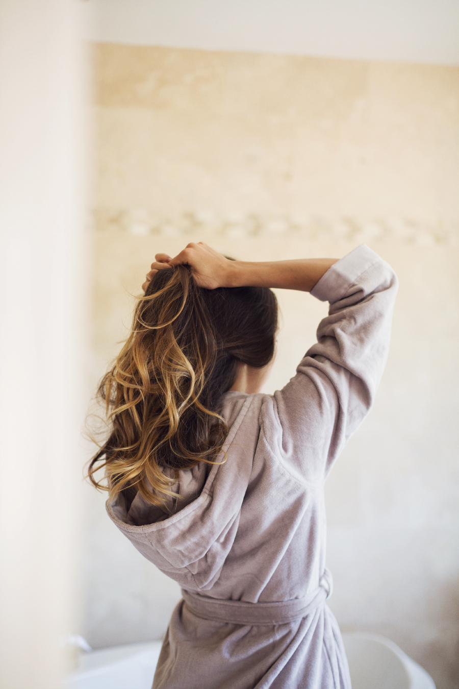 Girl in bathrobe with ombre brown blonde hair pulling her hair up