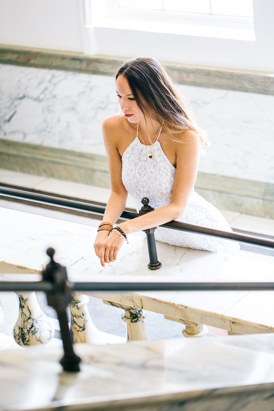 White dress photoshoot on marble staircase